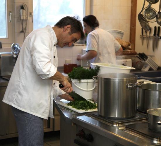 Koch schneidet Petersilie in der Großküche